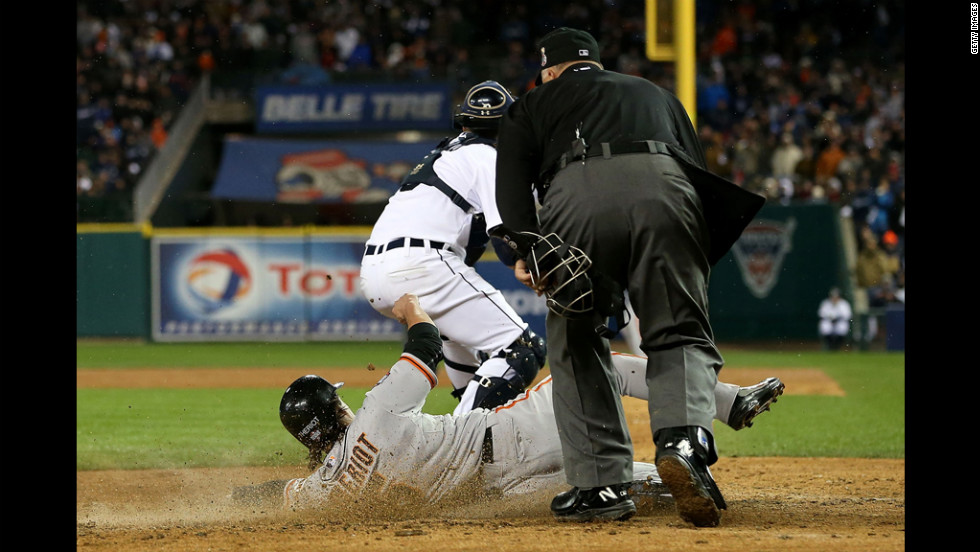 Ryan Theriot of the San Francisco Giants slides to home in the tenth inning.