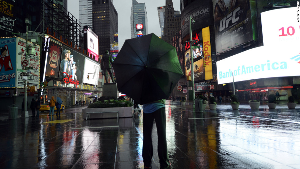 A  tourist stands in Times Square early Monday, October 29, as New Yorkers prepare to endure Hurricane Sandy.