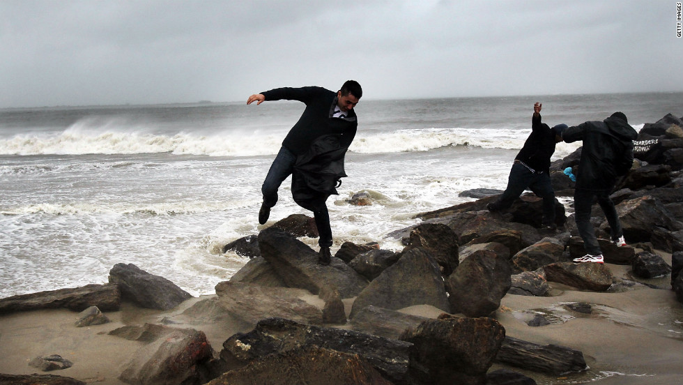 People fight against the wind along Brighton Beach in New York on Monday.