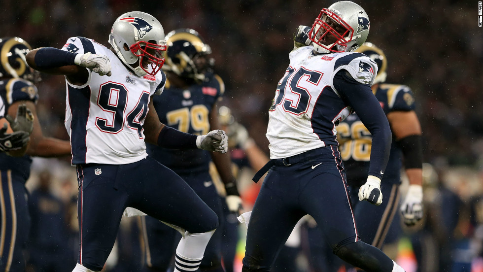 Justin Francis (94) and Patriots teammate Chandler Jones (95) celebrate after sacking the Rams' quarterback.