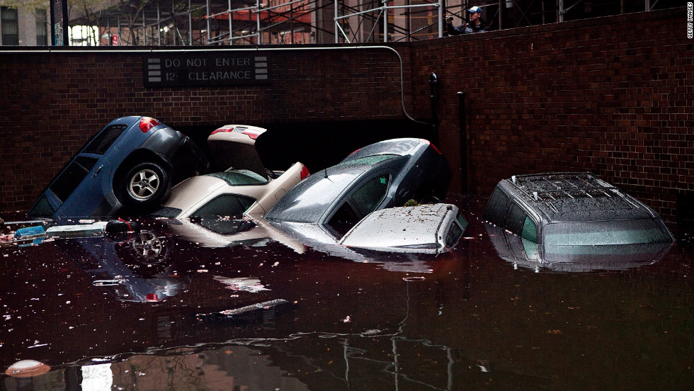 Cars float in a flooded below-street-level parking area in the Financial District on Tuesday.
