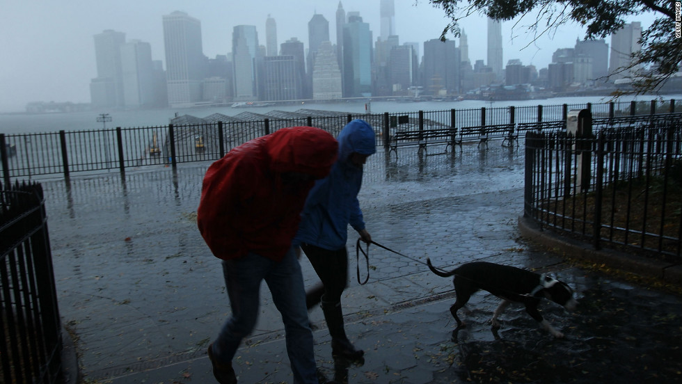 A couple walks in the rain Tuesday, with the East River and the Lower Manhattan skyline as a backdrop.