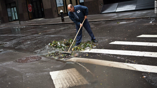 Ramiro Arcos sweeps debris from damage caused by Hurricane Sandy on Tuesday in New York's financial district.