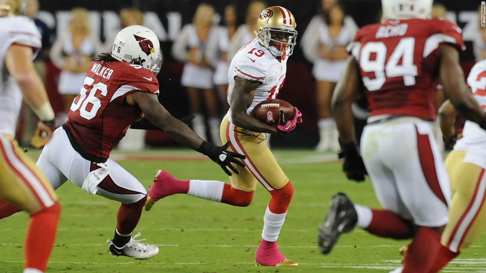 Ted Ginn Jr. of the San Francisco 49ers runs the ball past Reggie Walker of the Arizona Cardinals on Monday.