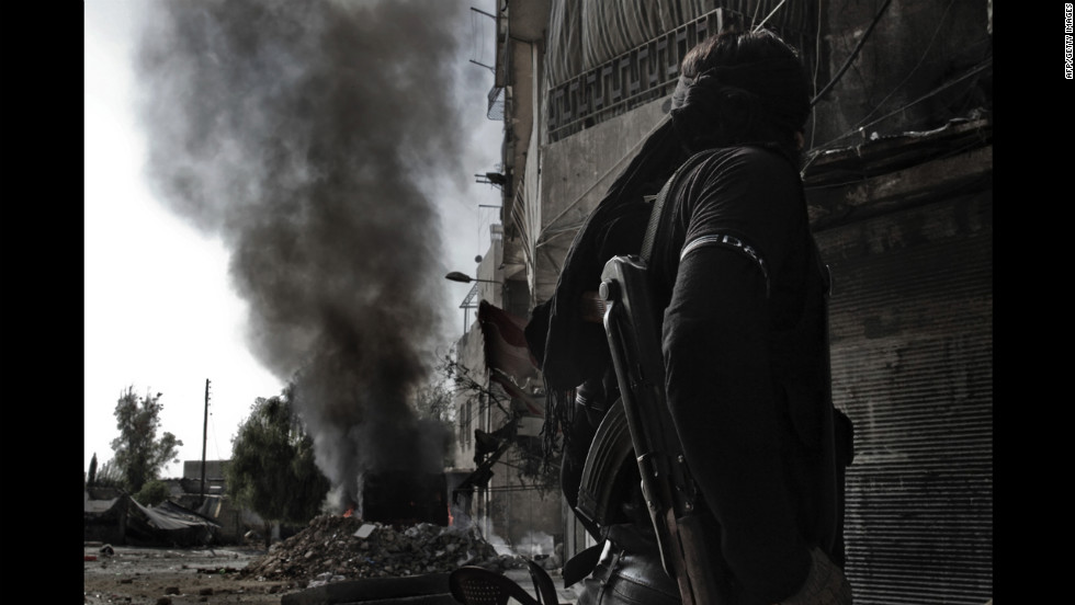 A Syrian rebel fighter looks at smoke billowing from a bus that caught fire after a regime sniper allegedly shot at it in Aleppo on Sunday, October 28.