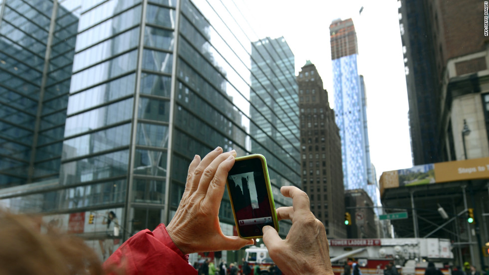 An onlooker snaps a photo of the damaged crane on Tuesday.