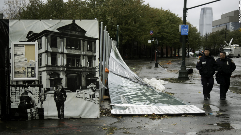 Police walk past debris left by the storm at Battery Park in New York on Tuesday.