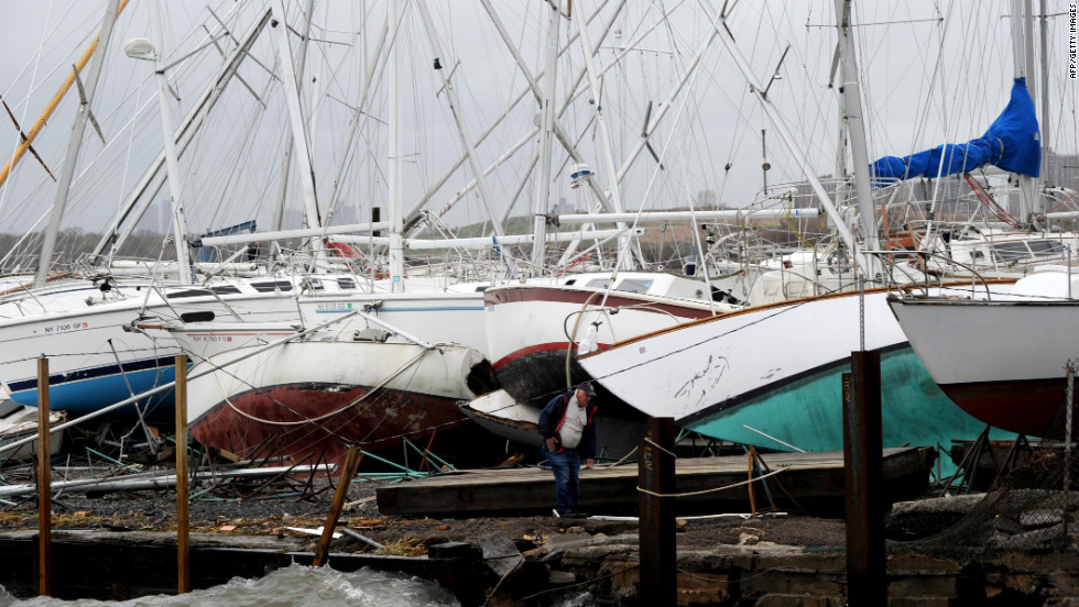 A man surveys damage to sailboats Tuesday at a marina on City Island in New York.