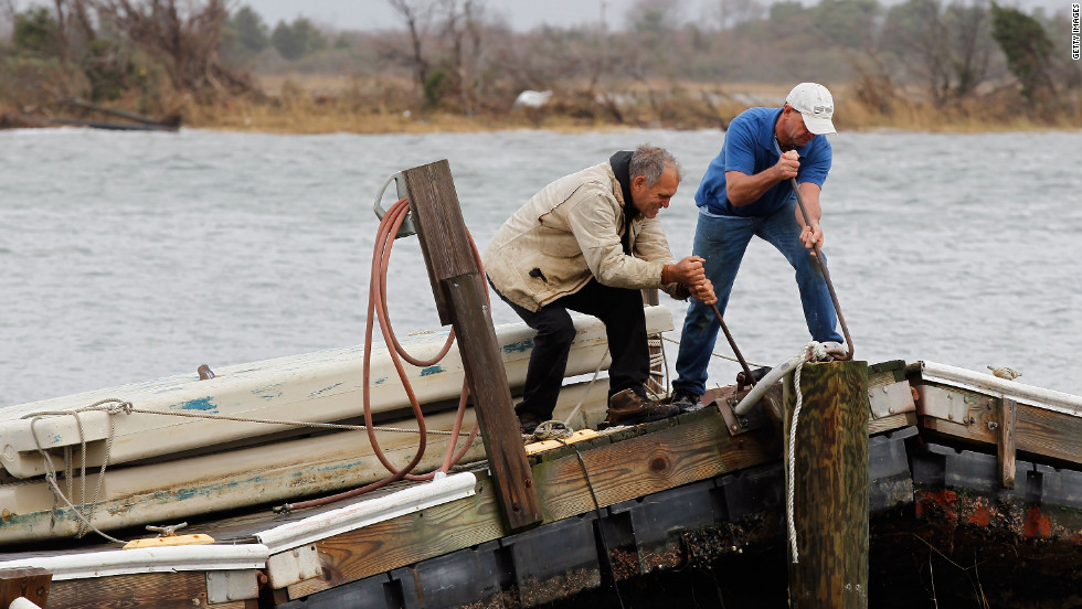 Ted Wondsel, left, of Point Lookout works on part of a dock destroyed in the storm in Long Beach on Tuesday.