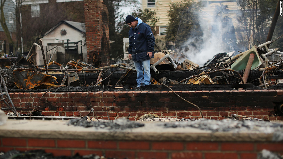 A  resident looks through the debris of his destroyed home in Breezy Point, Queens, on Tuesday.