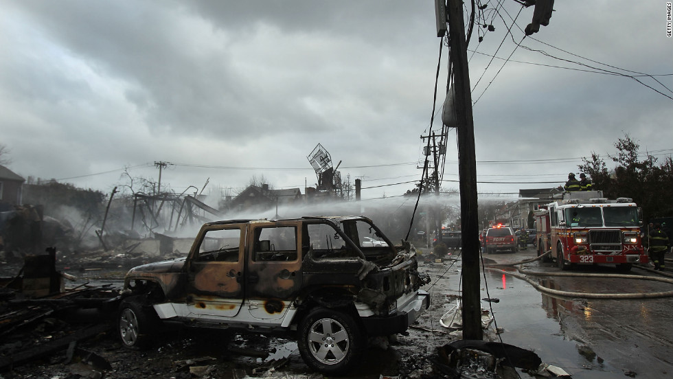Burned-out vehicles and destroyed homes line a street in Breezy Point, located on the western end of the Rockaway peninsula in New York.