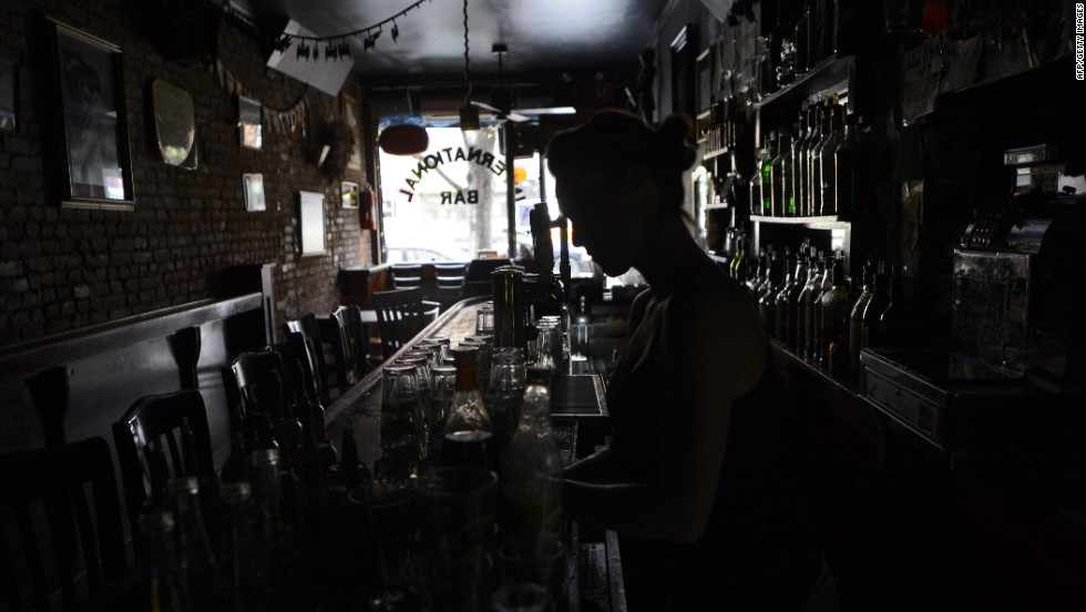 A bartender at the International Bar in the East Village neighborhood of New York City makes drinks in the dark on Tuesday as electricity remains out for many in the city.