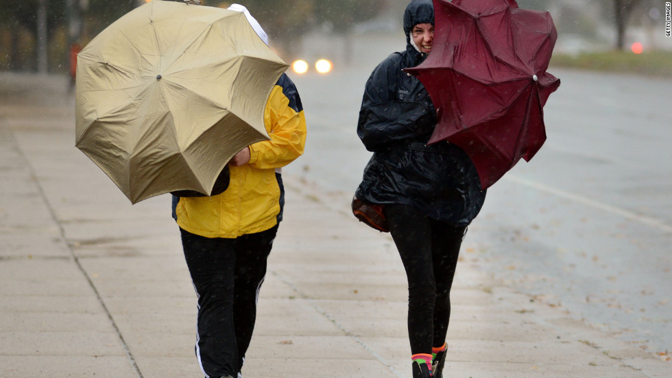 Two women battle wind and rain with umbrellas in hand in Philadelphia on Monday.