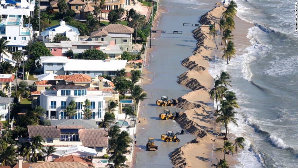 Work crews push sand from a roadway in Fort Lauderdale, Florida, due to storm surge related to flooding on Monday.