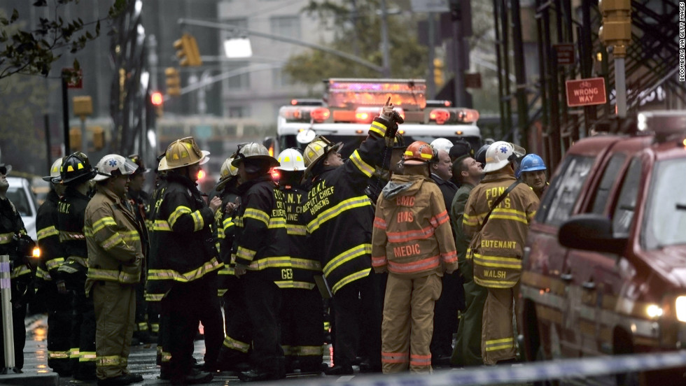 New York City firefighters and emergency workers view a collapsing crane hanging from a 90-story residential building in New York on Monday.