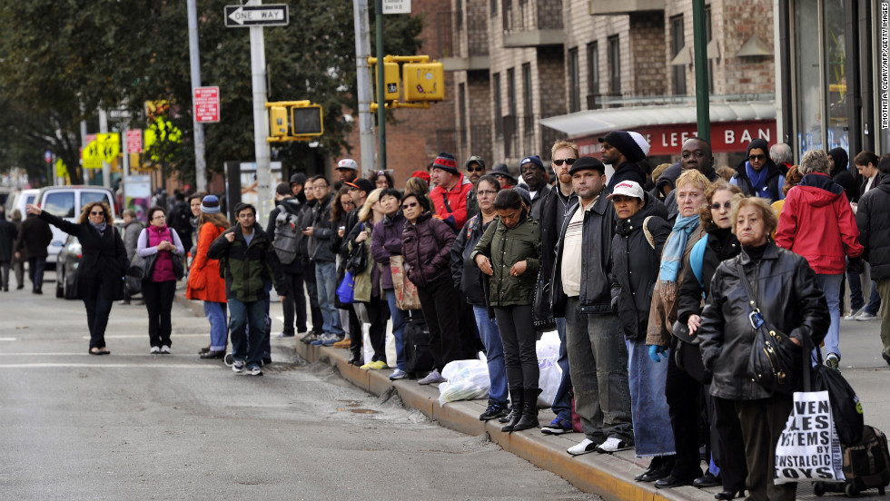 People wait for buses along  New York's Sixth Avenue on Wednesday.