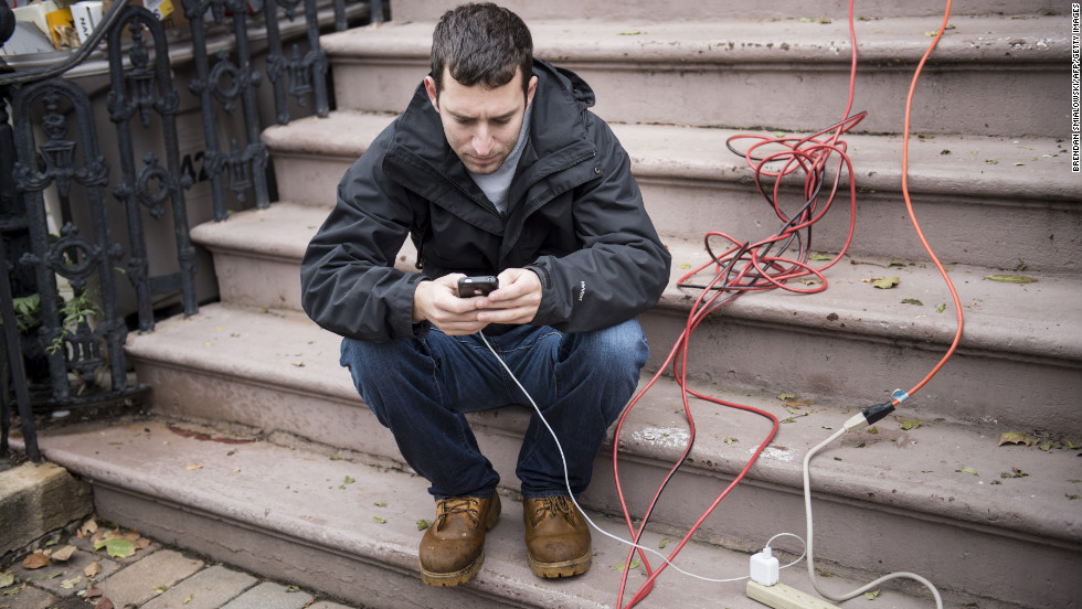 A man charges his cellphone at a home that still has power in Hoboken, New Jersey, on Wednesday, October 31. As of Wednesday afternoon, more than 2 million customers in New Jersey were without power.