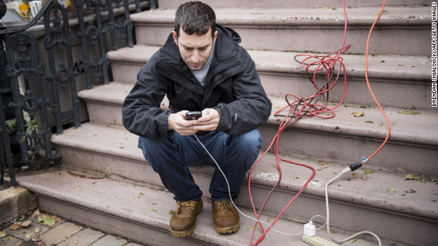 A man charges his cellphone from an extension cord from a home Wednesday that still had power in Hoboken, New Jersey.