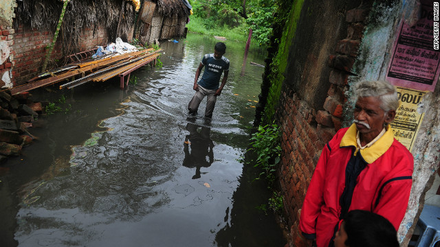 An Indian man wades through a flooded street in Chennai on October 31, 2012.