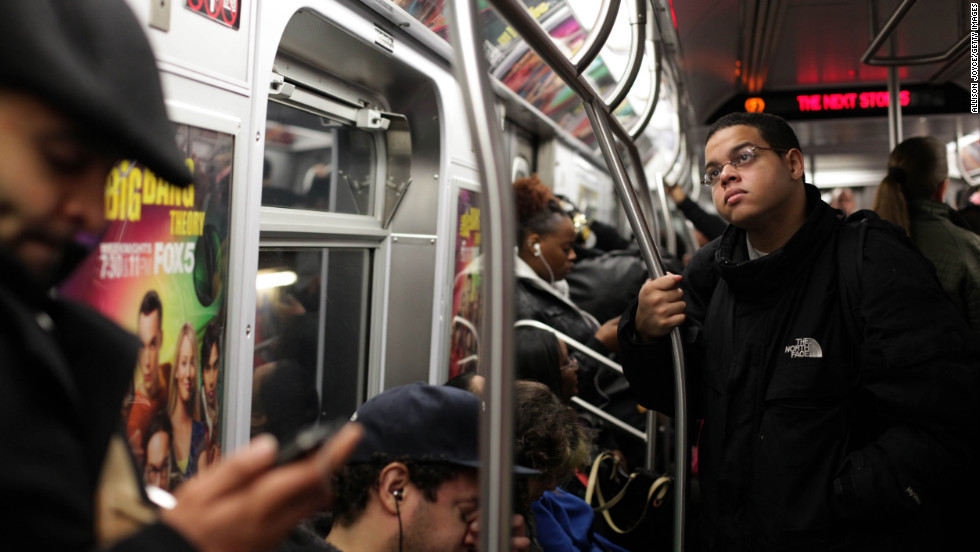 Commuters ride the subway. Public transit is operating in New York City, but travel times are long, up to five hours in some cases.