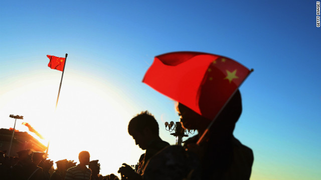 Tourists wait for the lowering of the flag at Tiananmen Square on September 29 in Beijing, China.