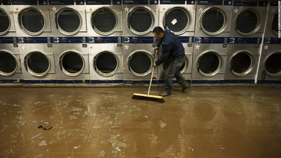 Eddie Liu uses a broom to clean up mud and water from a flooded coin laundry in Coney Island on Friday.