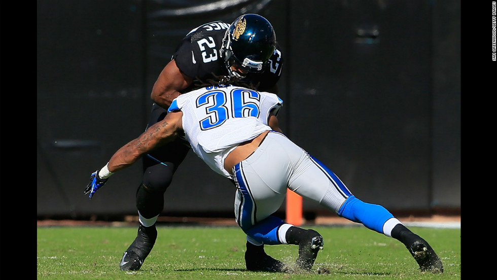Jonte Green of the Lions tackles Rashad Jennings of the Jaguars during the game on Sunday.