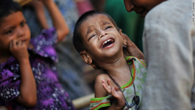 A Rohingya woman and her child wait for medical care outside a clinic in the Bawdupha camp, Sittwe on November 2, 2012.