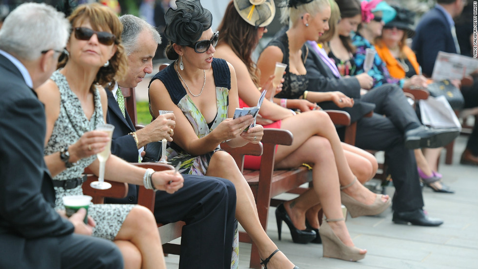 Racegoers in the members area study the form on Melbourne Cup Day.  Twenty-four horses will charge around the 3200 meter track for a total prize pool of $6 million and Australian fame and glory.