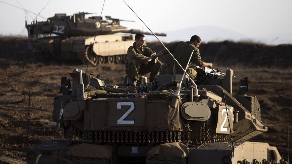 An Israeli Merkava tank crew sits in the Israeli-controlled Golan Heights overlooking the Syrian village of Breqa on Tuesday, November 6. An Israeli military vehicle in the Golan Heights was hit by gunfire from Syria on Monday, the Israeli army said.