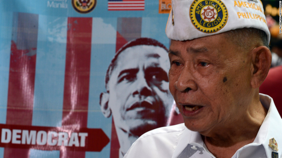 A Philippine World War II veteran speaks to reporters next to a portrait of the newly-re elected president, Barack Obama of the Democratic party during a mock US election vote, spearheaded by the US embassy at a shopping mall in Manila on November 7, 2012. US President Barack Obama was re-elected, television networks projected -- only the second time in several decades that a Democrat has won a second term in the White House.    AFP PHOTO/TED ALJIBE        (Photo credit should read TED ALJIBE/AFP/Getty Images)
