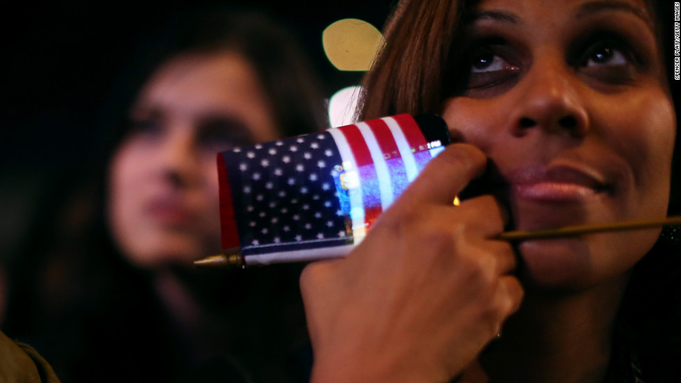 An Obama supporter clutched a flag and a smart phone at an election night rally in Chicago.