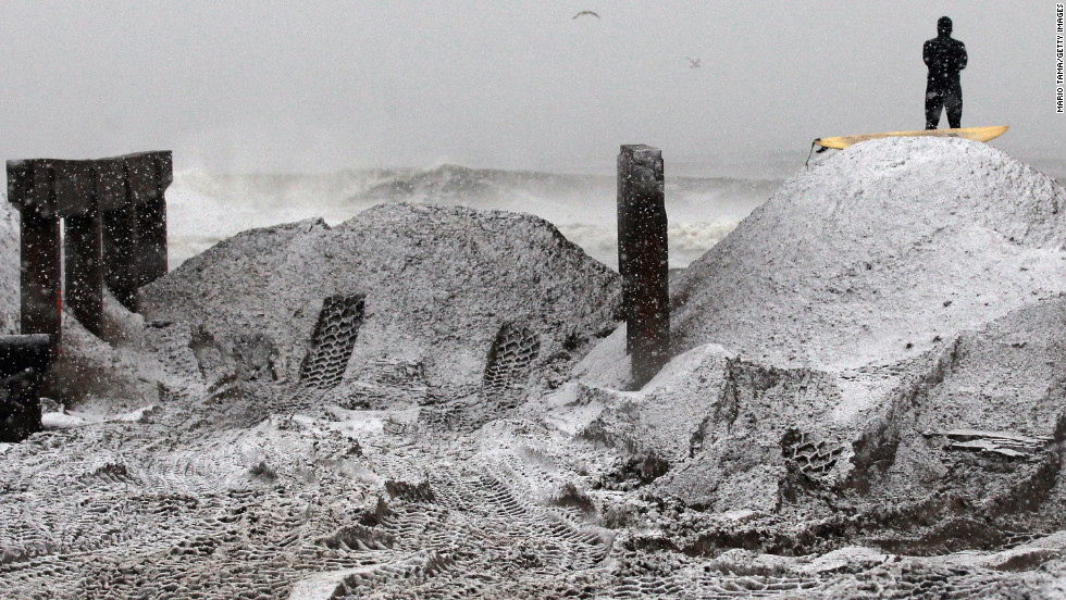 ''Mandog'' watches the surf from a pile of sand beside the destroyed boardwalk in Rockaway area on Wednesday. Sand had been collected from the streets and placed on the beach to clear the roads and to help prevent possible storm surge.