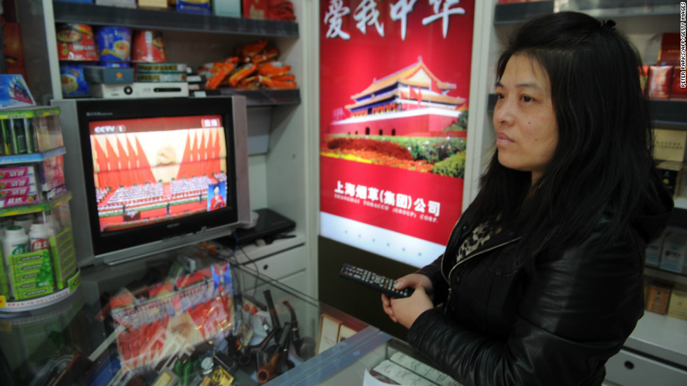 A woman watches the Party Congress on television from her cigarette shop in Shanghai.
