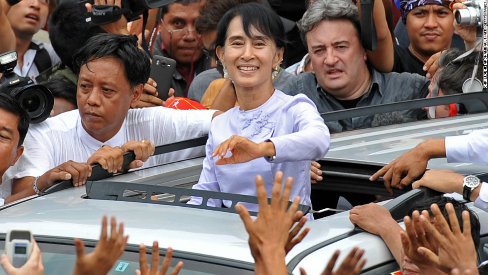 Myanmar opposition leader Aung San Suu Kyi waves to the crowd as she leaves National League for Democracy  headquarters in Yangon on April 2. She hailed a 'new era' for Myanmar and called for a show of political unity after her party claimed a major victory in landmark by-elections.