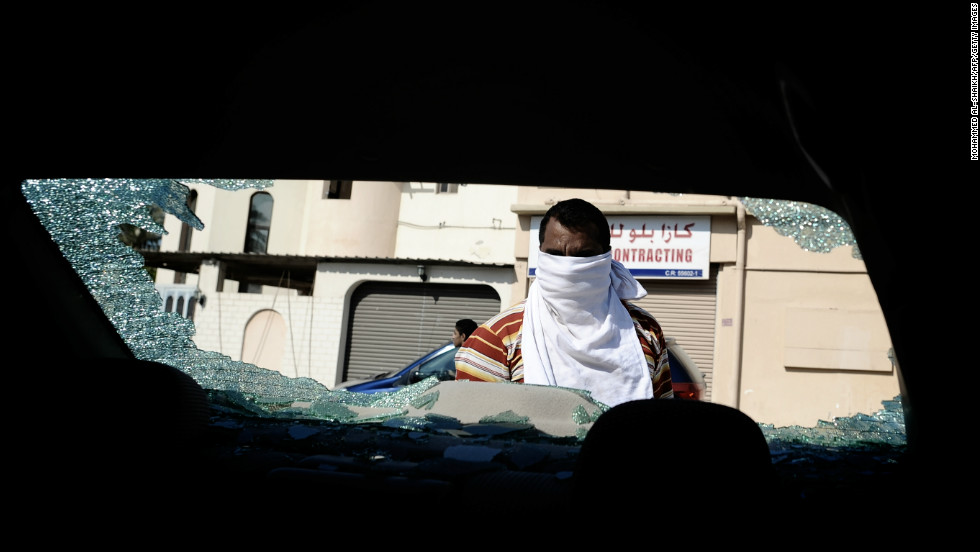 A Bahraini Shiite man inspects his car, which was damaged during clashes between riot police and protesters.