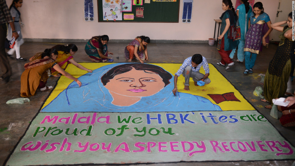 "Indian teachers add finishing touches to a ""Malala Rangoli"" at a high school in Ahmedabad on Saturday."