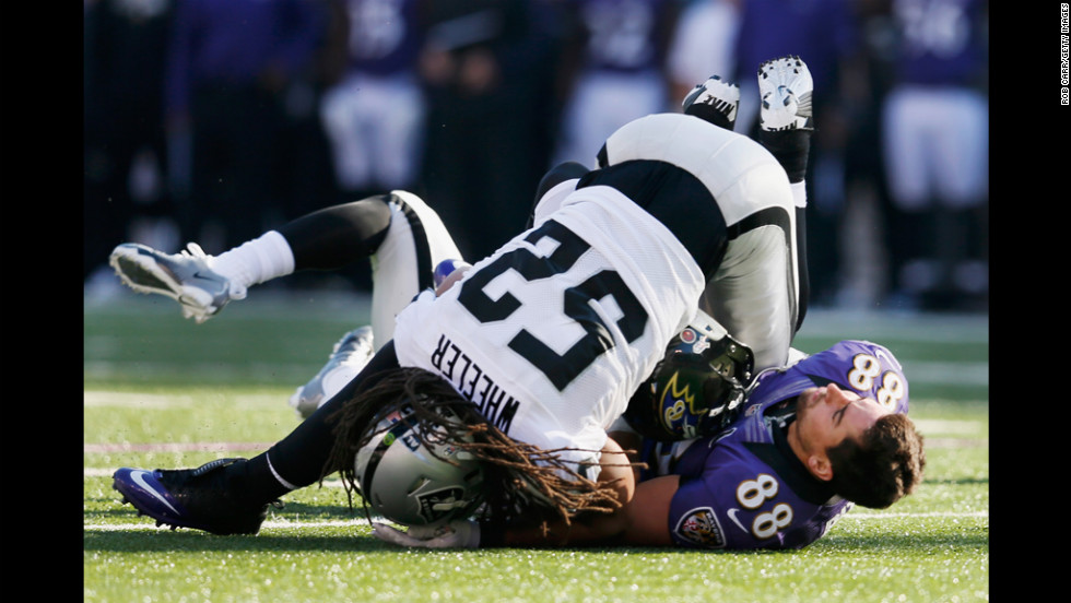 Tight end Dennis Pitta of the Ravens loses his helmet after catching a pass and being tackled by outside linebacker Philip Wheeler of the Raiders during the first half on Sunday.