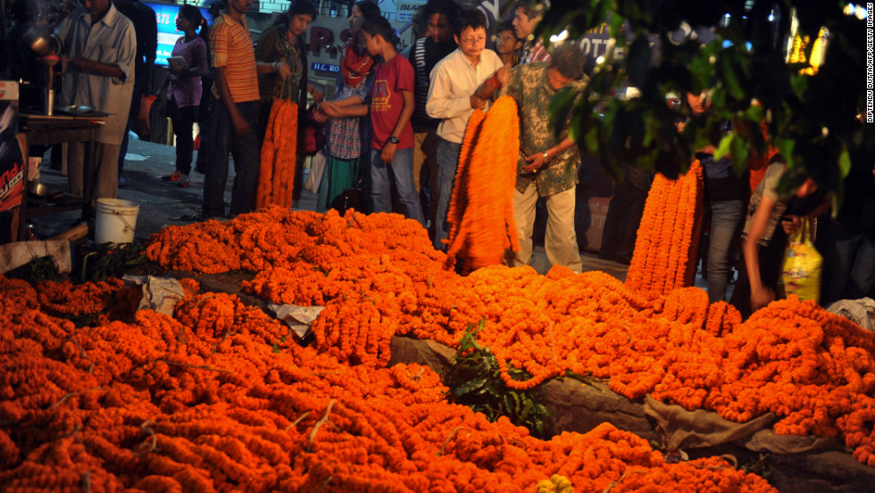 Indian flower sellers display garlands of marigolds at a roadside stall in Siliguri on Monday, November 12.
