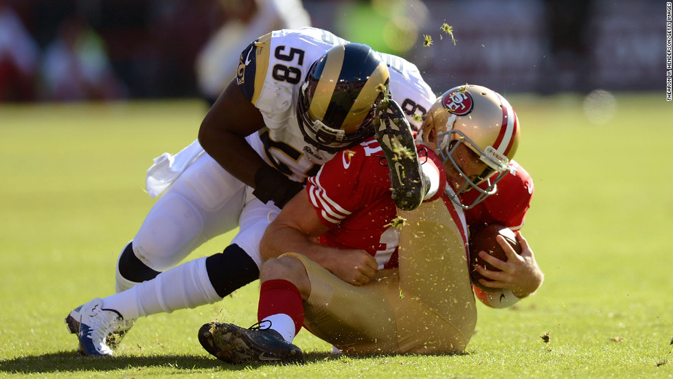 Alex Smith of the San Francisco 49ers is hit hard by Jo-Lonn Dunbar of the St. Louis Ram during the first quarter of their game on Sunday.