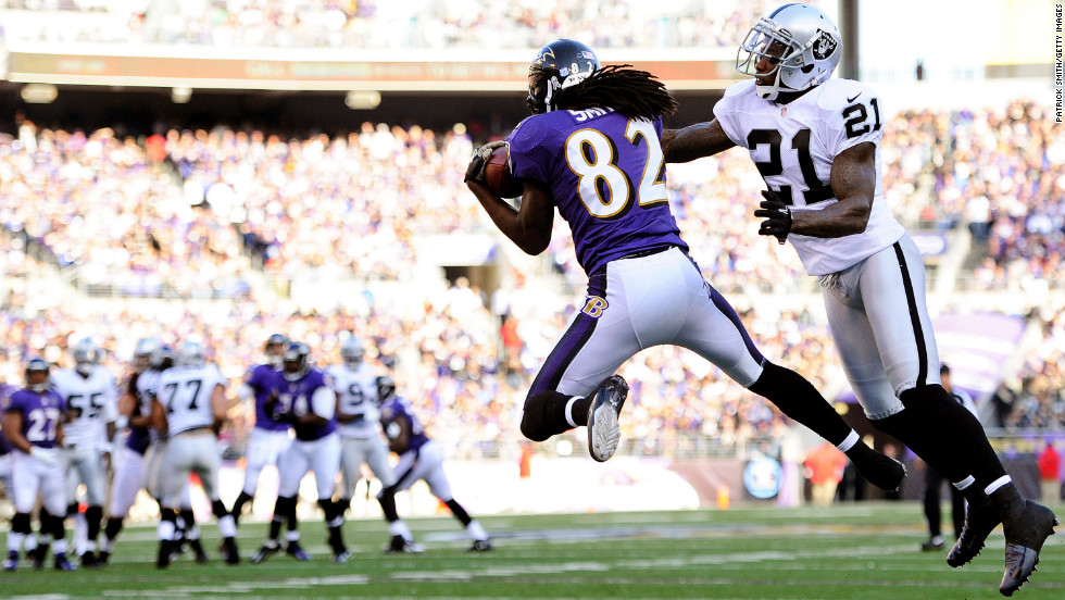 Wide receiver Torrey Smith of the Baltimore Ravens catches a pass for a touchdown past cornerback Ron Bartell of the Oakland Raiders in the third quarter at M&T Bank Stadium on Sunday in Baltimore.