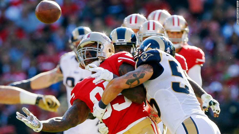 Tight end Vernon Davis of the 49ers bobbles a catch before pulling in the ball as he gets hit by linebacker James Laurinaitis of the Rams in the second quarter on Sunday.