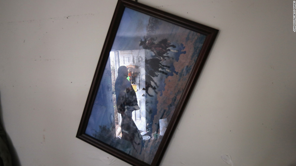 A family friend of a drowning victim of Superstorm Sandy looks through household debris in New York on Tuesday, November 13.