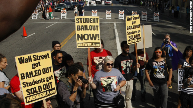 "Demonstrators symbolically ""burn"" student loan bills in Los Angeles during a protest of rising student loan costs."