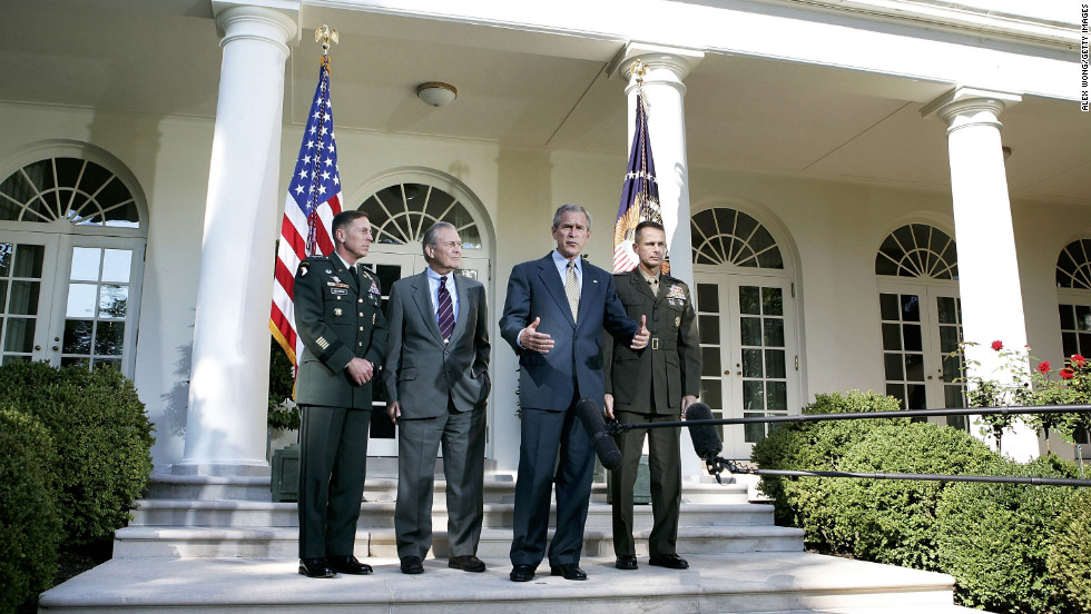 Lt. Gen. Petraeus, left, listens to President George W. Bush after Bush met with top military officials to discuss the war in Iraq in October 2005.