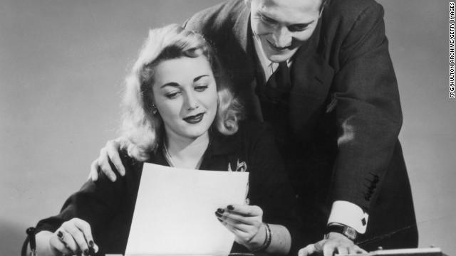 A businessman reads a document over his secretary's shoulder, circa 1935