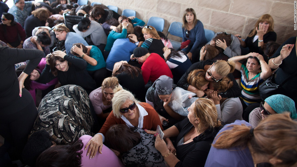 People take cover during a rocket attack at a funeral Friday, November 16, in Kiryat Malakhi, Israel.