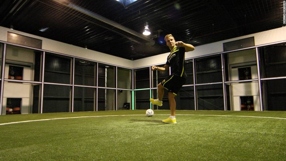 "Once inside the ""Footbonaut"", a player is fed balls by eight different machines and then has deliver the ball to one of the 72 panels - - which is indciated by a flashing green light -- that make up the space-age contraption before they receive another ball. This picture shows Dortmund's German star Mario Gotze testing himself against the machine."