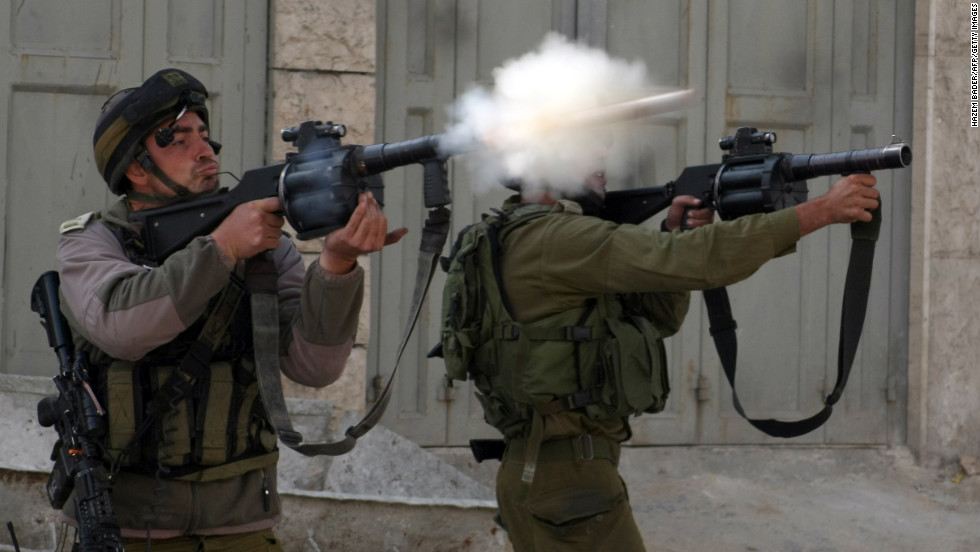 Israeli soldiers fire tear gas toward stone throwers demonstrating against the Israeli military offensive in Gaza in the village of Beit Omar, north of the West Bank town of Hebron, on Saturday, November 17. Egypt and Turkey put the onus on Israel to end the fighting around Gaza as Turkish Prime Minister Recep Tayyip Erdogan visited Cairo a day after Washington urged the two governments to pressure the Palestinians.