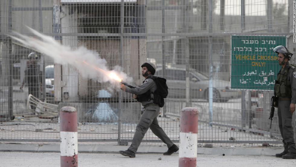 Israeli soldiers fire tear gas toward strone throwers demonstrating against the Israeli military offensive on the Gaza Strip at the Qalandia checkpoint, in the occupied West Bank, on Saturday, November 17. Israeli strikes on Gaza destroyed the Hamas government headquarters as Israel called up thousands more reservists for a possible ground war.